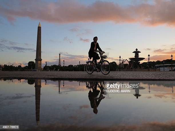 A woman rides her bicycle at sunset on the place de la Concorde in Paris on May 13 2014 in Paris AFP PHOTO / LUDOVIC MARIN