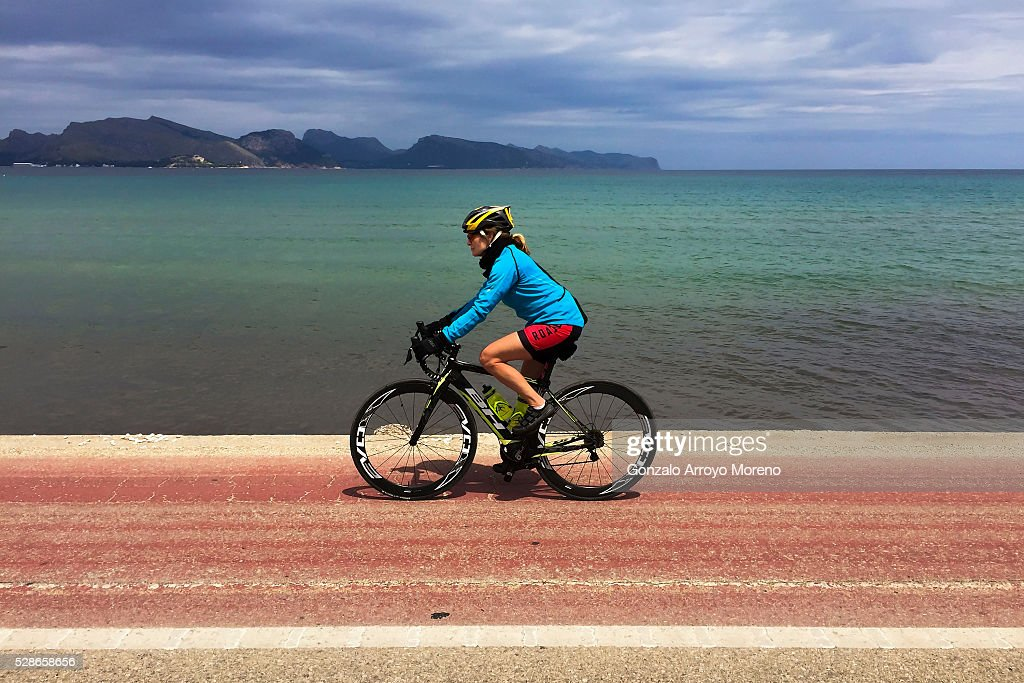 A woman rides her bike ahead Collerassa beach the day before Ironman 70.3 Mallorca on May 6, 2016 in Palma de Mallorca island, Spain.