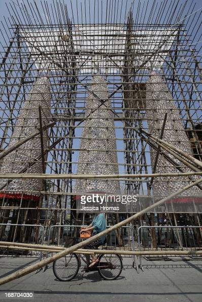 A woman rides her bike past the Cheung Chau Bun Festival towers which are still under scaffolding on May 14 2013 in Hong Kong Hong Kong Today is the...