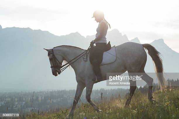 Woman rides horse down mountain slope