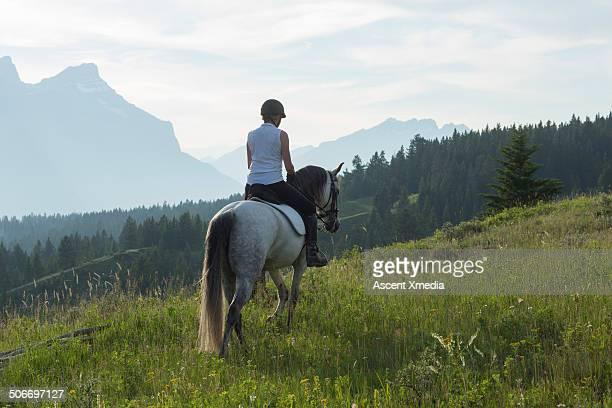 Woman rides horse through mountain meadow