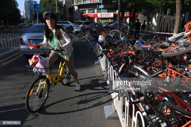 A woman rides in a car lane past a stack of shared bicycles blocking the cycle lane on a street in Beijing on August 3 2017 China on August 3 issued...