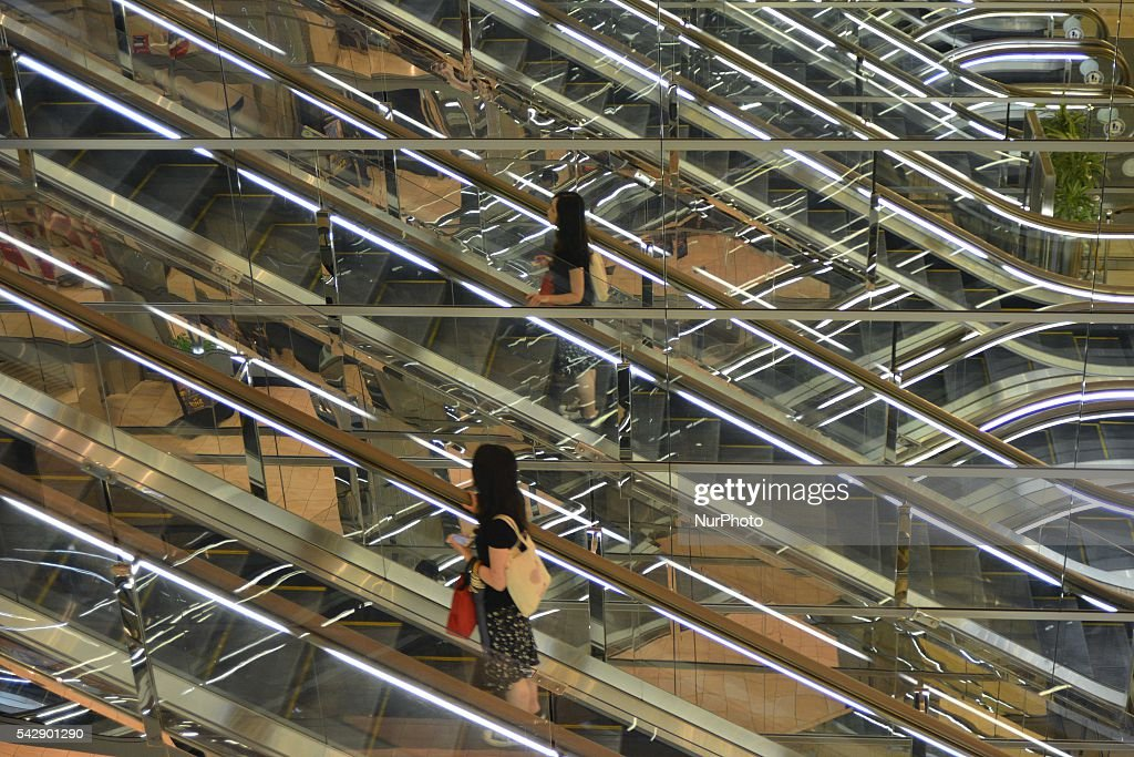 A woman rides on an escalator at a business district in Tokyo June 25, 2016.