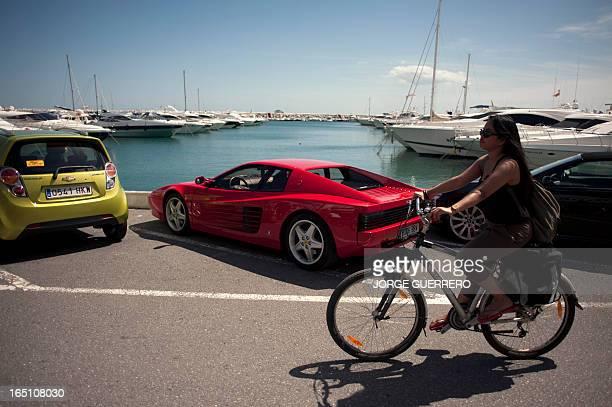 A woman rides past a Ferrari car in Puerto Banus near Marbella on March 30 2013 AFP PHOTO / JORGE GUERRERO