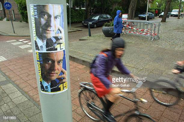 A woman rides past an election poster for the late Pim Fortuyn a day before national elections May 14 2002 in Rotterdam the Netherlands Campaigning...