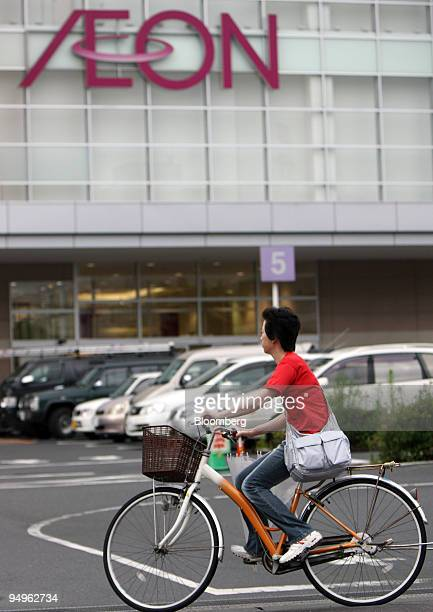 A woman riding a bicycle enters an Aeon Co shopping center in Toda City Saitama Prefecture Japan on Monday July 6 2009 Aeon Co is expected announce...