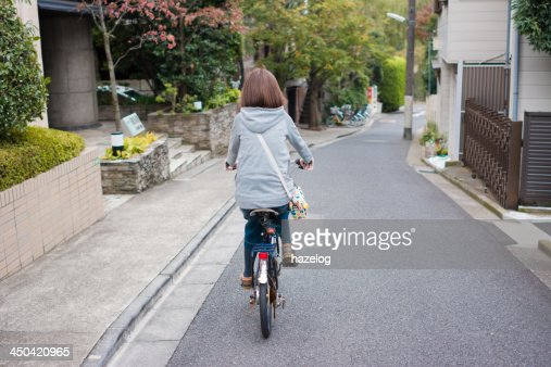 Woman riding a bike in residential area : Stock Photo