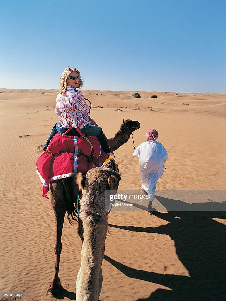 Woman Riding a Camel Following a Man in Traditional Middle Eastern Dress