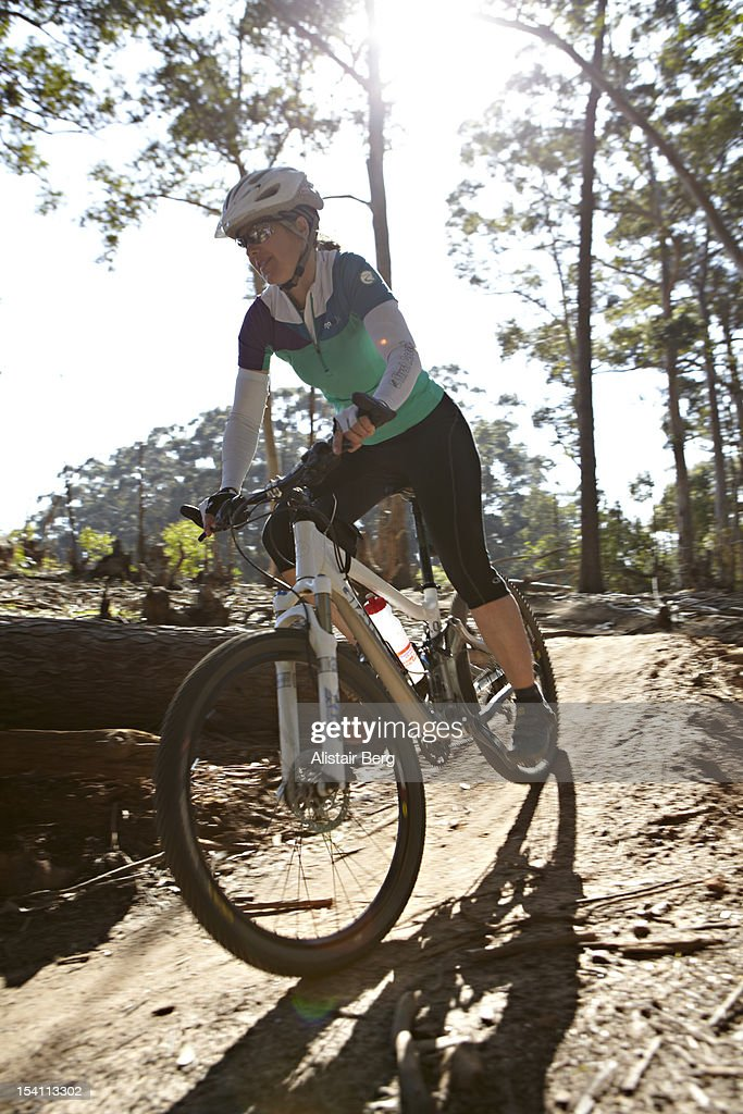 Woman riding a mountain bike downhill : Stock Photo