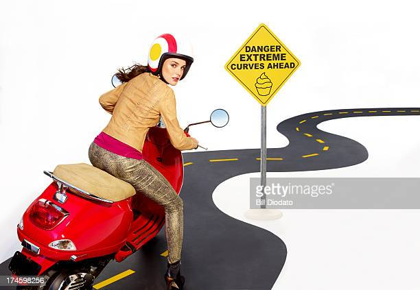 Woman riding a scooter in curvy road