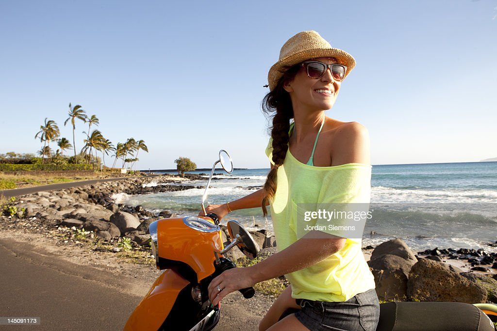 Woman riding a scooter on a tropica island.