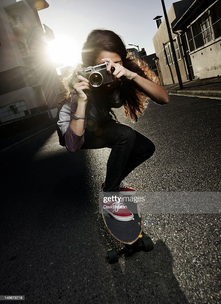 Woman riding a skateboard and taking a photograph : Stock Photo
