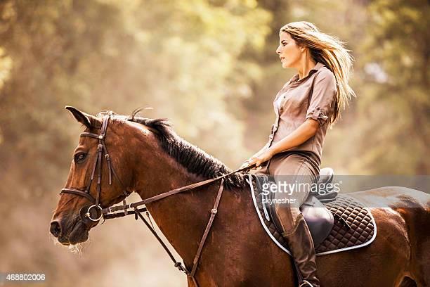 Mulher que monta um cavalo ao ar livre.