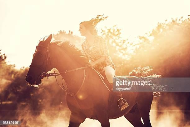 Mujer montando una stallion al aire libre.