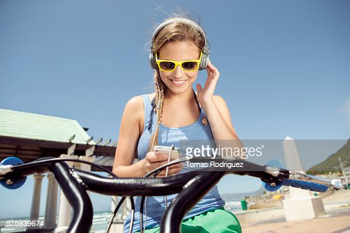 Woman riding bicycle and listening to music on smart phone : Stock Photo