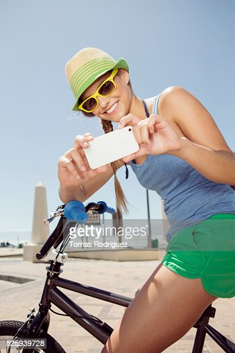 Woman riding bicycle and taking picture with cell phone : Stock Photo