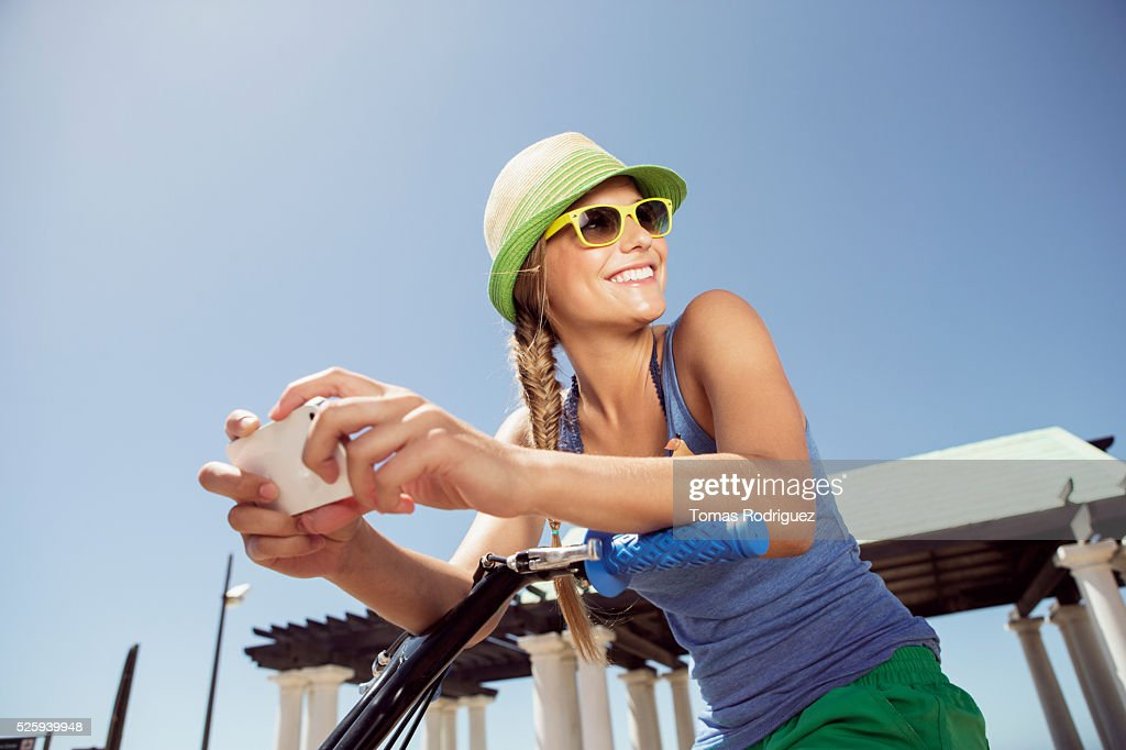 Woman riding bicycle and text messaging : ストックフォト