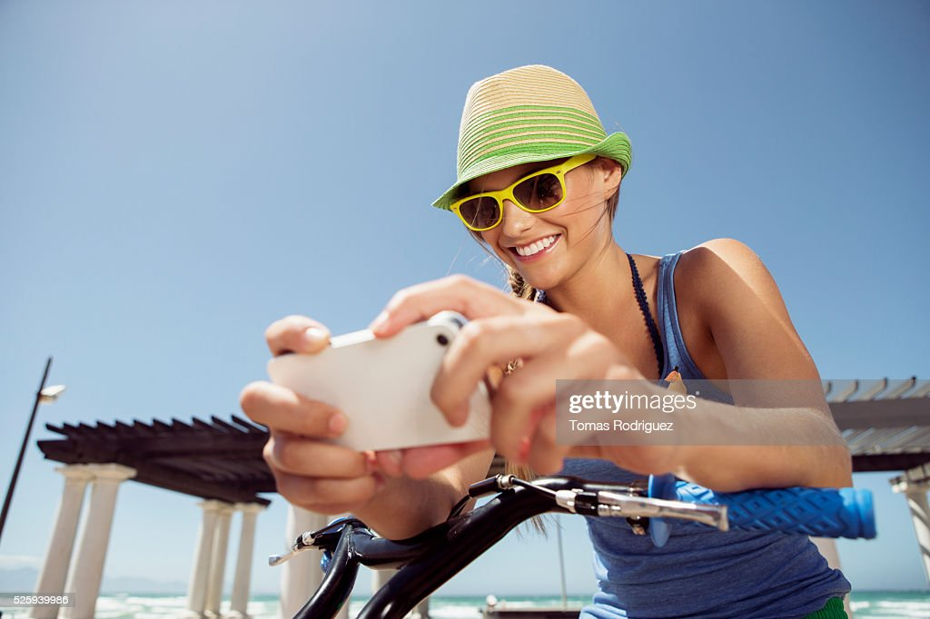 Woman riding bicycle and text messaging : Foto de stock