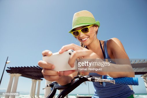 Woman riding bicycle and text messaging : Stockfoto