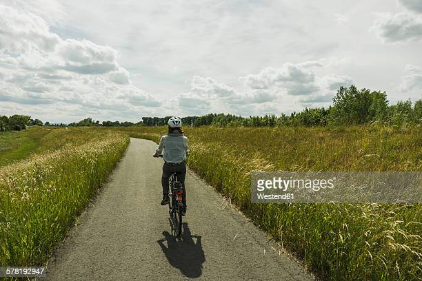 Woman riding bicycle at countryside