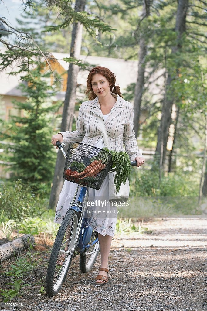 Woman riding bicycle in countryside : Stockfoto