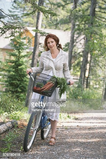 Woman riding bicycle in countryside : Stock Photo