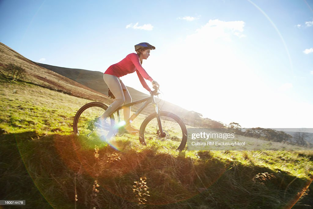 Woman riding bicycle in grassy field : Stock Photo