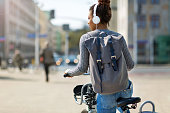 Young woman riding bicycle in city