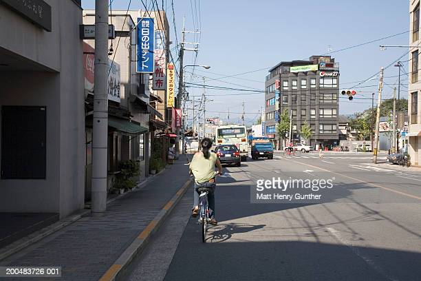 Woman riding bicycle on city street, rear view