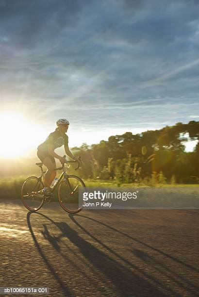 Woman riding bicycle on coutry road at sunset, side view