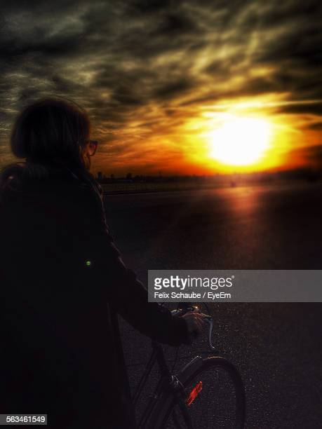 Woman Riding Bicycle On Street Against Cloudy Sky During Sunset