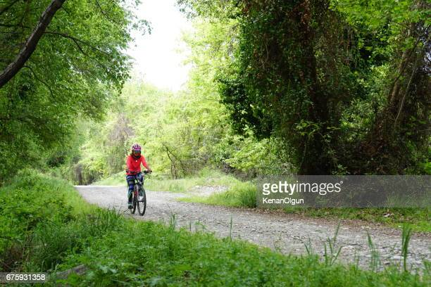 Woman riding bicycle on the forest road