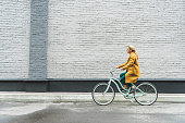 fashionable woman in yellow coat riding bicycle with grey wall on background
