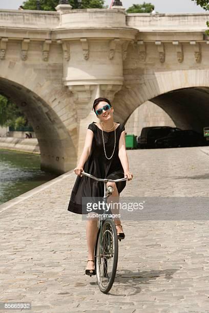 Woman riding bicycle , River Seine , Paris , France