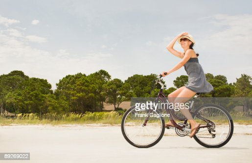 Woman Riding Bike Along Beach. : Photo