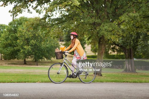 Woman Riding Bike In Park Stock Photo