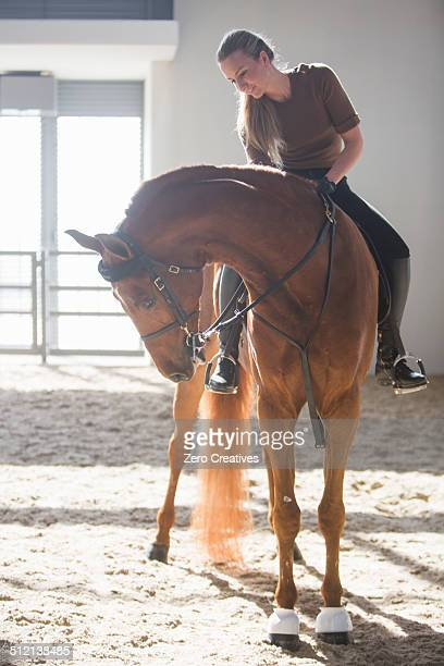 Woman riding chestnut horse in indoor paddock