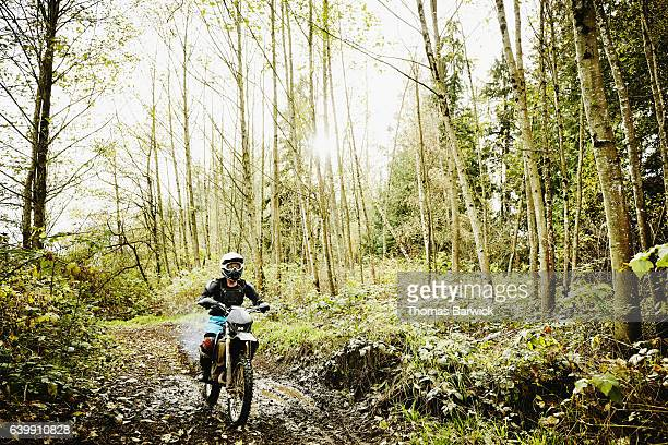 Woman riding dirt bike through forest trail on fall afternoon