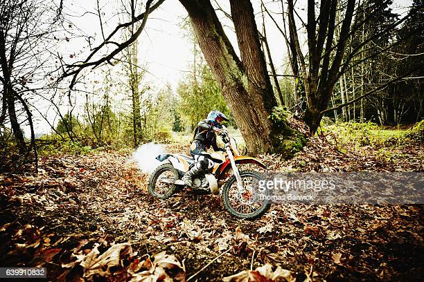 Woman riding dirt bike through leaves in forest on fall afternoon