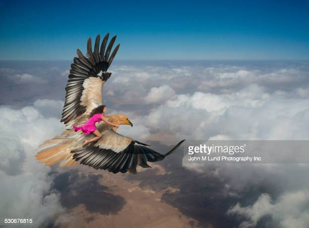 Woman riding eagle flying over clouds in sky