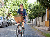 woman riding her bicycle on cobblestone street