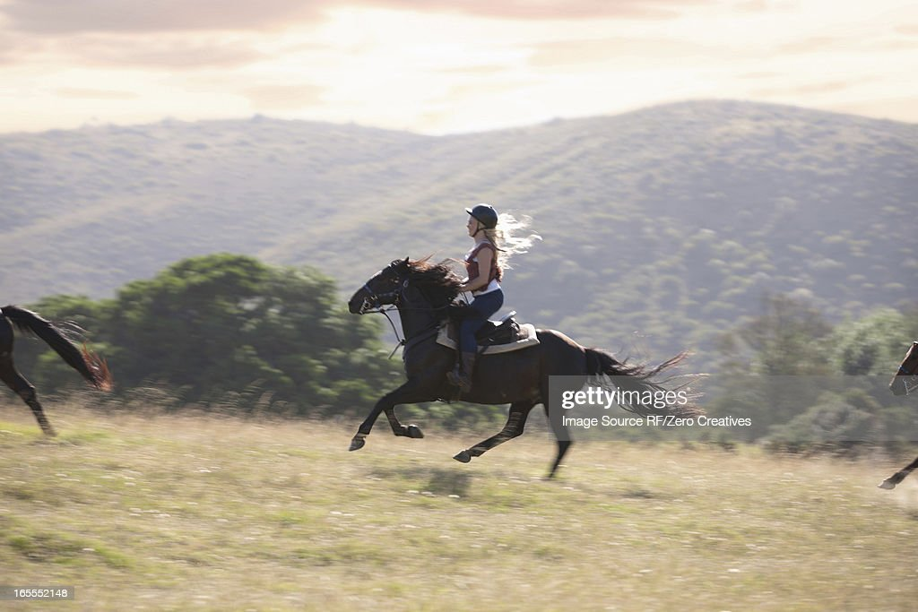 Woman riding horse in rural landscape