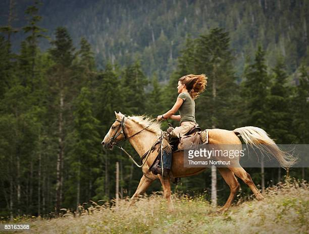 Woman riding horse through field.