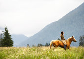 Frau Reiten Pferd durch Feld.