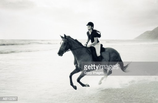 Woman riding horseback on beach