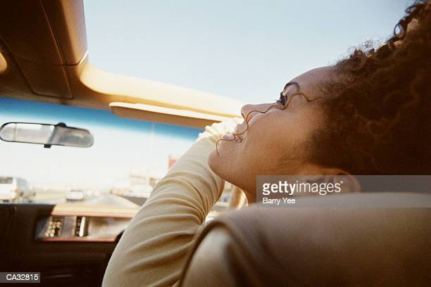 Woman riding in car, looking through sunroof