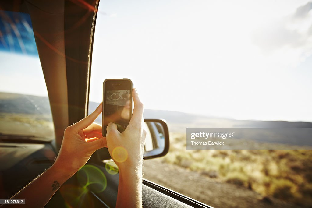 Woman riding in car taking photo with smartphone : Stock Photo