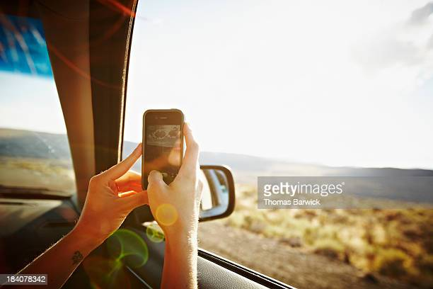 Woman riding in car taking photo with smartphone