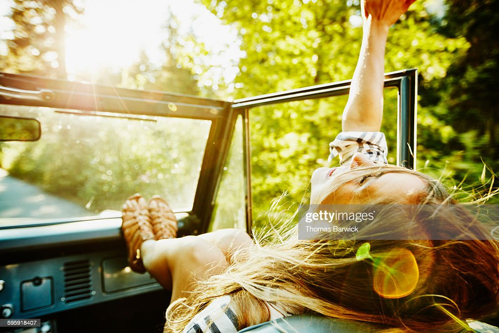 Woman riding in passenger seat of convertible : Foto stock