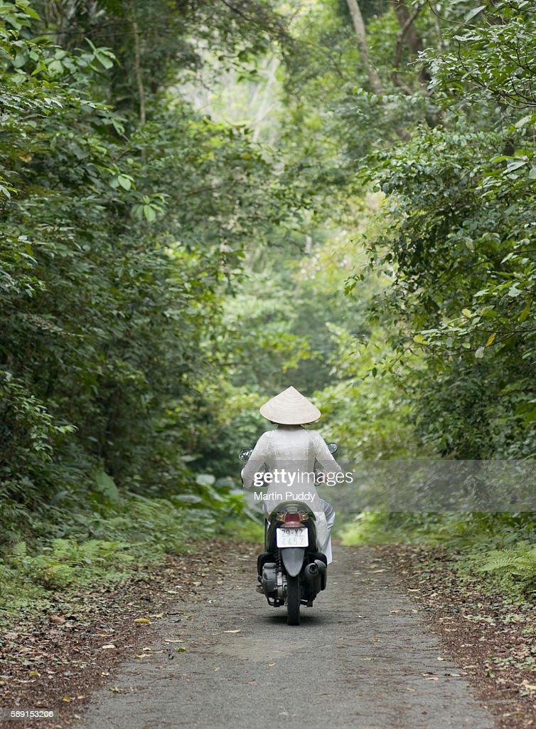 Woman riding motorscooter through jungle